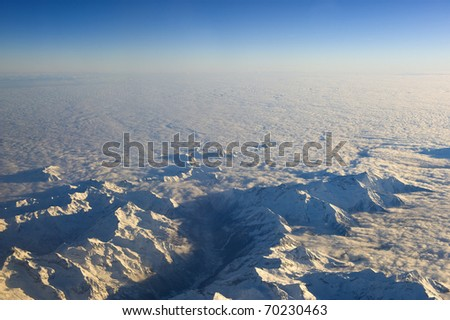 High altitude view of the Dolomites poking above the cloud layer. - stock photo