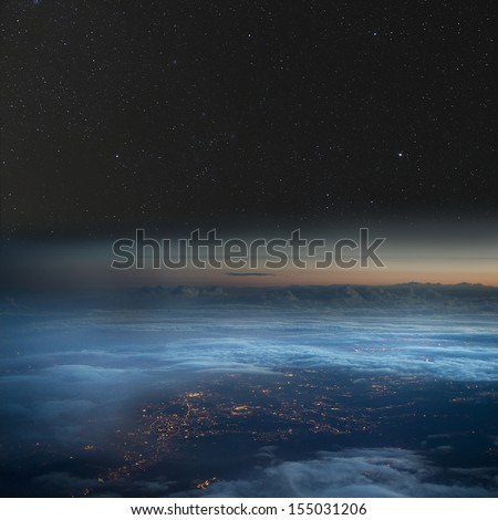 High altitude view of the Earth at night. City lights below the clouds, stars above. - stock photo