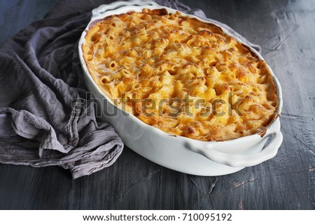 High angel view of a dish of fresh baked macaroni and cheese with table cloth and old wood spoon over a rustic dark background.