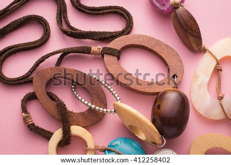 High Angle Close Up Still Life of Handmade Artisan Necklace on Pink Background - Detail of Fashionable Jewellery with Wooden Circles and Colorful Beads and Stones Secured with Leather - stock photo