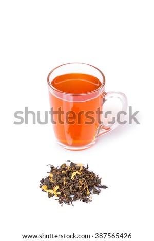 High Angle Close Up View of Orange Colored Herbal Tea in Glass Mug on White Background with Pile of Mixed Gourmet Tea Leaves