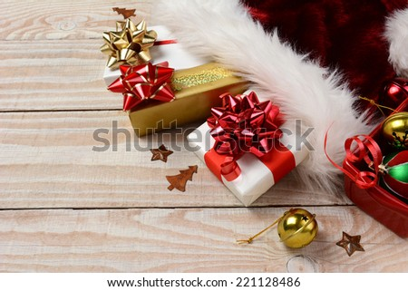 High angle closeup of Christmas presents and Santa Claus hat on a rustic white wood table. Horizontal format with copy space. - stock photo