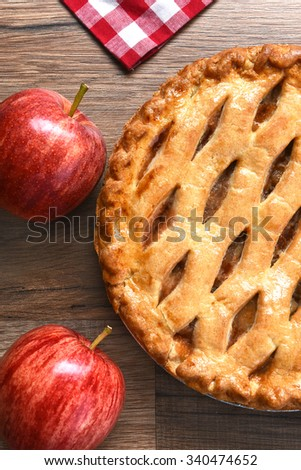 High angle closeup view of a fresh baked apple pie with apples on a rustic wood table. Vertical format. - stock photo