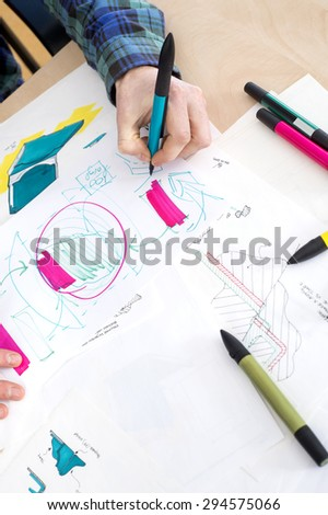 High angle cropper image of artist's hand drawing sketch on paper in creative focus - stock photo