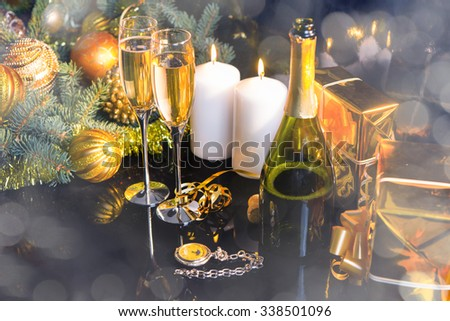High Angle Festive Still Life - Two Glasses of Sparkling Champagne with Bottle, Candles, Gifts, Pocket Watch and Christmas Decorations on Black Background with Shimmering Effect - stock photo