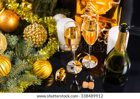 High Angle Festive Still Life - Two Glasses of Sparkling Champagne with Bottle, Candles, Gifts and Christmas Decorations on Black Background - stock photo
