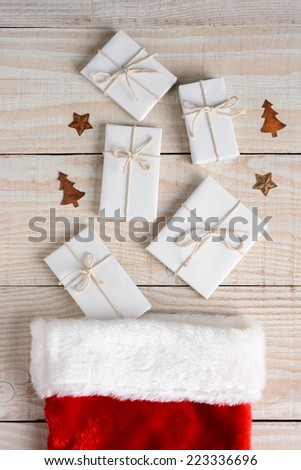 High angle image of a Christmas Stocking with five plain white paper wrapped gifts tied with string on a whitewashed wood table. Vertical Format. - stock photo