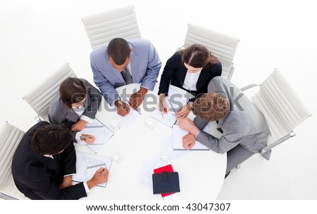 High angle of a diverse business group sitting around a conference table in a meeting - stock photo