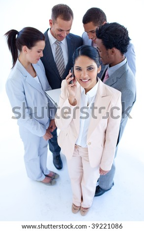 High angle of businesswoman talking on mobile phone in front of her team - stock photo