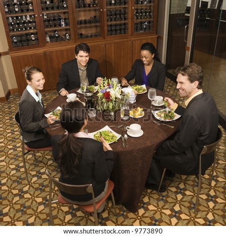 High angle of group of businesspeople in restaurant dining. - stock photo