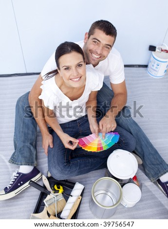 High angle of happy couple choosing colours to paint new house - stock photo