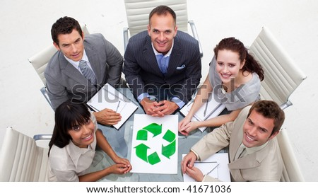 High angle of smiling business team holding a recycling symbol in the office - stock photo