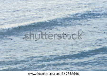 High angle of surfers crowded in the big surf breaker zone of Torrey Pines beach in Southern California