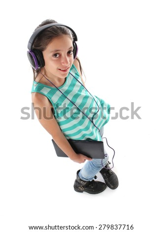 High angle picture for a beautiful pre-teen girl using a tablet computer and headphones. White background - stock photo