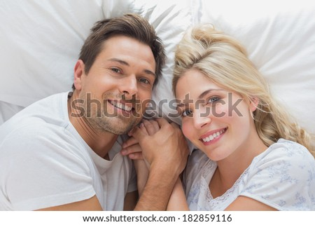 High angle portrait of a relaxed loving couple lying in bed at home - stock photo