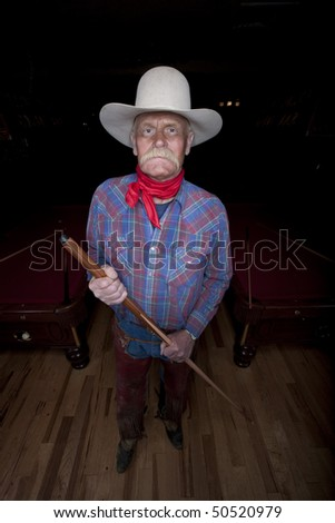 High angle portrait of a senior man in western wear, holding a pool cue and standing in a pool hall. He is looking at the camera with a serious expression. Vertical format. - stock photo