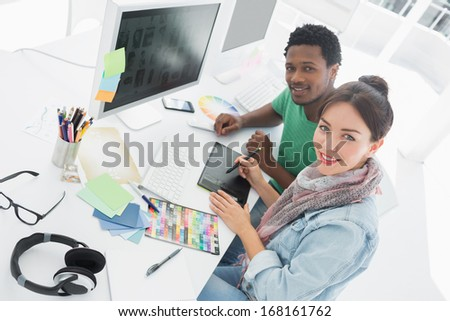 High angle portrait of an artist with colleague drawing something on graphic tablet at the office - stock photo