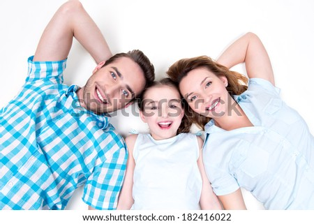 High angle portrait of caucasian happy smiling young family with two children lying down on white floor and looking at camera - stock photo