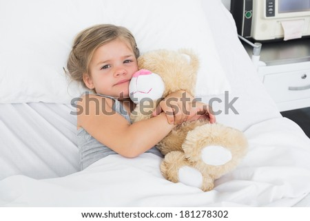 High angle portrait of cute girl embracing teddy bear while lying in hospital bed - stock photo