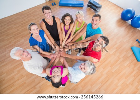 High angle portrait of fit people stacking hands at health club - stock photo