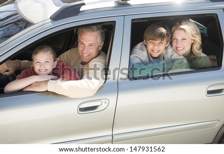 High angle portrait of happy family sitting in car - stock photo