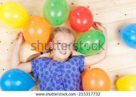 High angle portrait of little girl with colorful balloons lying on floor - stock photo