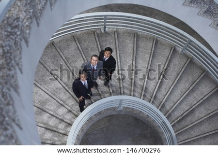High angle portrait of multiethnic business people standing on spiral staircase - stock photo