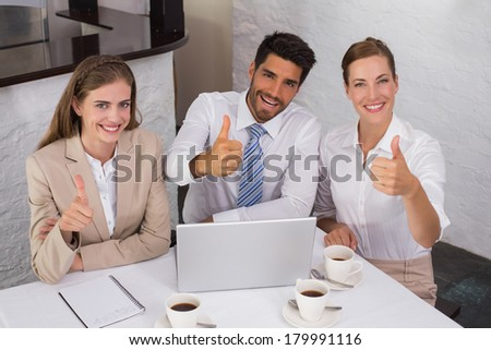 High angle portrait of young business people gesturing thumbs up at office desk