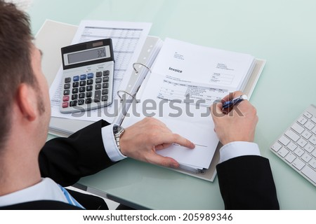 High angle portrait of young businessman calculating finance at office desk