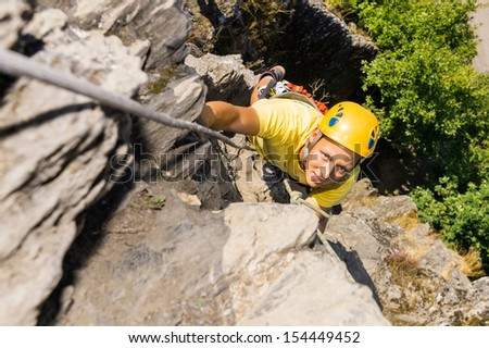 High angle portrait of young man climbing rock - stock photo