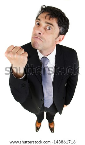 High angle portrait with diminishing perspective of a belligerent man making a fist and threatening the camera - stock photo