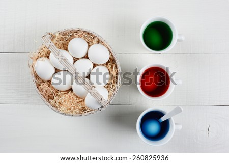 High angle shot of a basket full of eggs to be dyed for Easter. Three cups of dye with eggs soaking are next to the baskets of un-dyed eggs on a white wood kitchen table. - stock photo