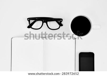 high-angle shot of a blank notebook, a pair of black plastic-rimmed eyeglasses, a cup of coffee and a smartphone on a white table - stock photo