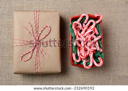 High angle shot of a bowl of mini candy canes next to a plain paper wrapped Christmas present on a burlap surface. The gift is tied with red and white twine. Horizontal Format. - stock photo