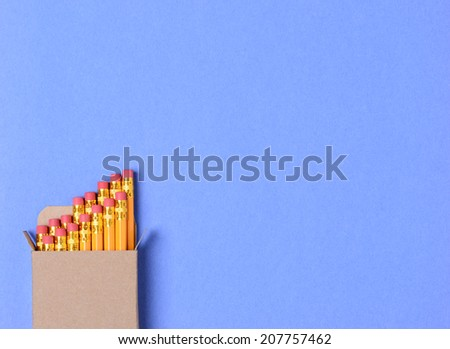 High angle shot of a box of new yellow pencils on a blue construction paper background. Horizontal format with copy space. Perfect for Back to School concepts. - stock photo