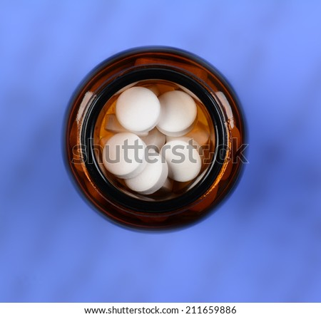 High angle shot of a brown glass pill bottle with white tablets. Shallow depth of field on a mottled blue background. - stock photo