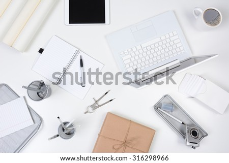 High angle shot of a business desk mock up. A neat white desk with objects either white or silver.  - stock photo