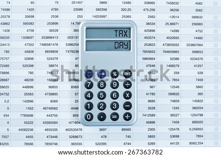 high-angle shot of a calculator with the text tax day in its display on a balance sheet - stock photo