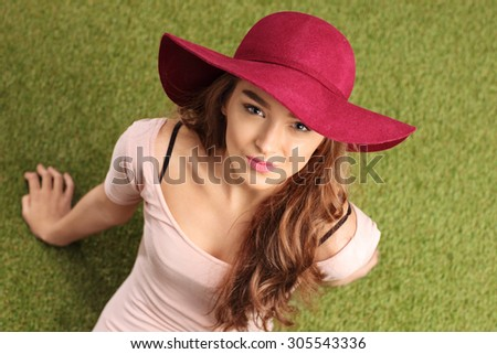 High angle shot of a cheerful young woman with a stylish hat sitting on grass and looking at the camera  - stock photo