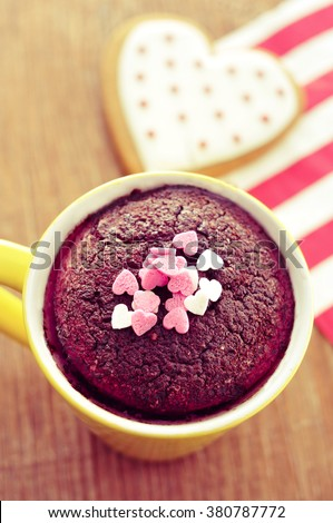 high-angle shot of a chocolate mug cake topped with heart-shaped confetti sprinkles and a heart-shaped cookie on a wooden table, with a filter effect - stock photo