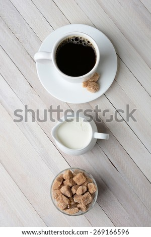 High angle shot of a cup of coffee, cream pitcher, and a bowl of natural sugar cubes. Vertical format on a rustic whitewashed table. - stock photo