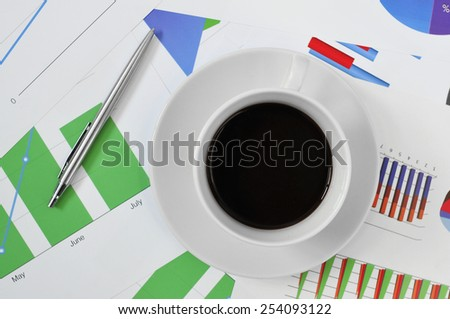 high-angle shot of a cup of coffee on a desk full of charts in the office - stock photo