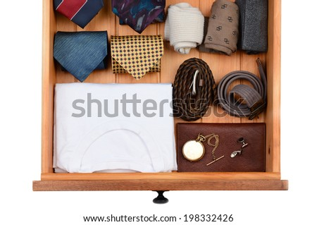 High angle shot of a dresser drawer with under shirts, belts, neck ties, socks, pocket watch and cuff links. Horizontal format isolated on white. - stock photo