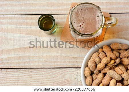 High angle shot of a glass of beer, a whiskey shot and a bowl of peanuts on a white wood table. Horizontal format with copy space. - stock photo