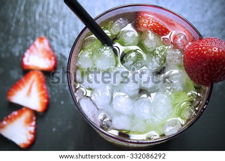 high-angle shot of a glass with a strawberry mojito garnished with a strawberry on a black slate background - stock photo