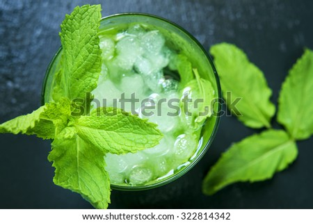 high-angle shot of a glass with an appetizing mojito garnished with a twig of mint on a black slate background - stock photo