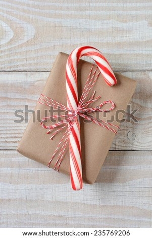 High angle shot of a large candy cane on a small plain brown paper wrapped Christmas present. Vertical format on a rustic white wooden table. - stock photo