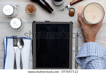 High angle shot of a man holding his glass of beer on a restaurant table with a table computer menu for ordering. Only the man's hand and arm are visible. - stock photo