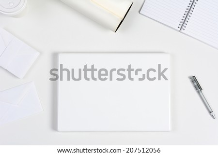 High angle shot of a neat white desk with primarily white office objects. Items include, a closed laptop computer, pad, pens, coffee cup, and envelopes. - stock photo