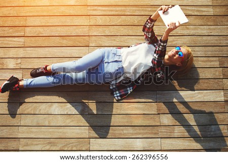 High angle shot of a pretty young woman pouting for a self-portrait while lying on wooden jetty enjoying the sun, cute tourist girl taking self-ie with digital tablet camera outdoors, flare sun light - stock photo